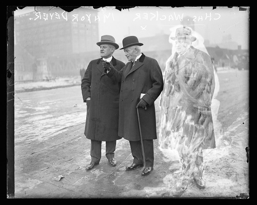 Informal full-length portrait of Charles Wacker, Chairman of the Chicago Plan Commission, and William Emmett Dever, Mayor of Chicago from 1923-1925, standing outdoors in Chicago, Illinois, during a meeting to discuss plans for a centennial celebration of the city's 1833 incorporation. The celebration became the 1933 World's Fair Century of Progress. Wacker is pointing to the left of the camera, and a building is visible in the background.