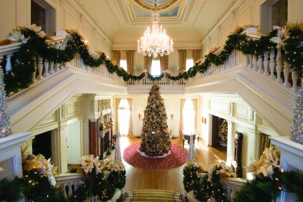 "GLANWORTH GARDENS: The Great Hall is the focal point of the house and includes a 20-foot artificial tree decorated, last year, with Christopher Radko ornaments, hand blown glass ornaments, flickering 4"" candles tucked throughout the tree, and sprinkled with faux snow from top to bottom. The bannister combines gold-trimmed poinsettias, gold pine branches and gold mesh. The Great Hall's fireplace, one of 11 in the home, is decorated with gold pine boughs, red ornaments, gold and red ribbon, and a variety of ornaments."