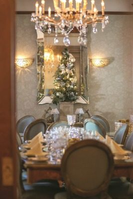 The dining room glows under the soft light of the room's crystal chandelier and wall sconces. The Venetian glass mirror as well as glass tabletops set with china and silver featuring different patterns makes for a sophisticated dining experience.