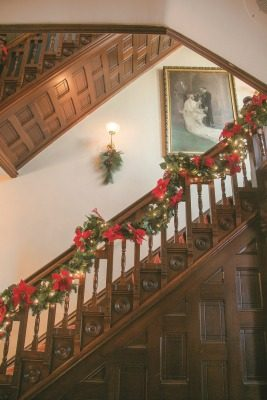 The home's main staircase to the second floor is made of four different woods, including cherry, and is wrapped with garland, ribbon and tiny lights during the holidays. A large, 4 ft. wide by 6 ft. high pastel watercolor painting purchased at an estate sale also hangs in the stairwell and serves as a perfect backdrop for wedding photos.