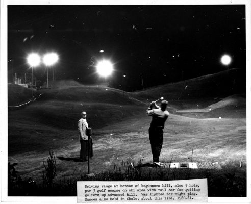 A driving range with 9-hole golf course is lighted for nighttime play.