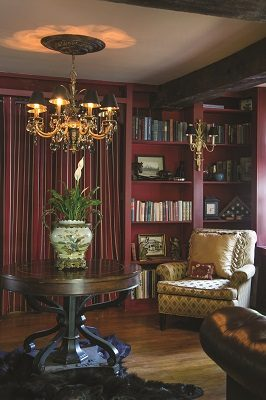 A can't-miss-it red wall of shelving in the library is filled with antiquities and fascinating books, while the opposite walls in a soothing, neutral color complement the home's original post and beam construction and its collection of artwork.